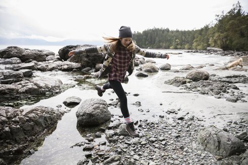 Playful teenage girl jumping over rock on rugged beach - HEROF14423