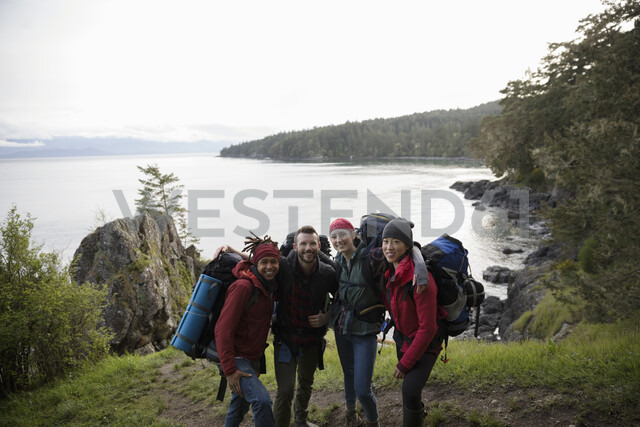 Portrait happy friends backpacking on cliff overlooking ocean - HEROF14429
