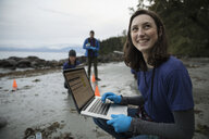Portrait smiling, confident eco-friendly female scientist with laptop on beach - HEROF14432