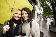Portrait smiling women friends with coffee under yellow umbrella - HEROF14453