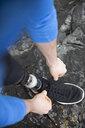 Overhead view male amputee runner tying shoe - HEROF14477