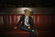 Portrait playful, humorous male millennial wearing horse head in nightclub - HEROF14513