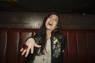 Portrait playful, laughing female millennial with candy ring in nightclub - HEROF14519