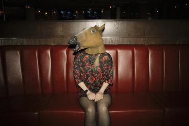 Portrait female millennial wearing horse head in nightclub - HEROF14528