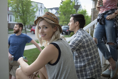 Portrait smiling woman relaxing with friends on front stoop - HEROF14564