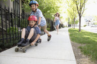 Playful boy pushing brother on skateboard on neighborhood sidewalk - HEROF14570