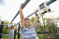 Playful boy swinging from monkey bars at playground - HEROF14573