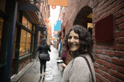 Portrait smiling, confident woman with coffee in urban alley - HEROF14597