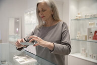 Senior jewelry boutique business owner using camera phone to photograph display - HEROF14606