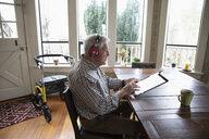 Senior man with headphones using digital tablet at dining table - HEROF14630