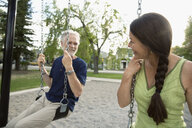 Smiling senior couple on swings at playground - HEROF14693