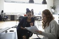 Female designers meeting, discussing paperwork in office - HEROF14723