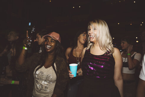 Female millennial friends drinking and partying in nightclub - HEROF14783