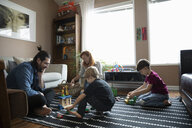Family playing with toys on living room floor - HEROF14795