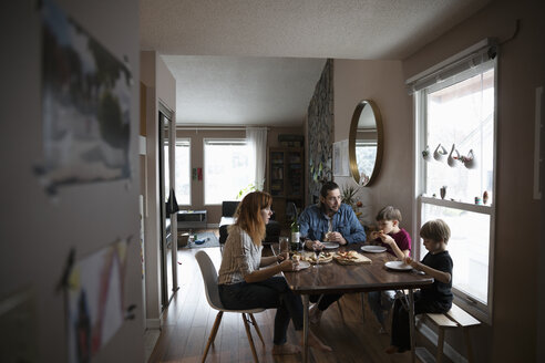 Family eating pizza at dining table - HEROF14807