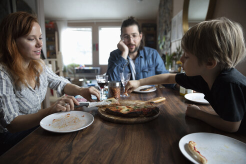 Family eating homemade pizza at dining table - HEROF14810