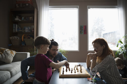 Family playing chess in living room - HEROF14813