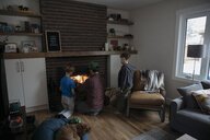 Father and sons building fire in living room fireplace - HEROF14825
