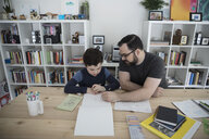Father and son drawing in notepad at table - HEROF14843