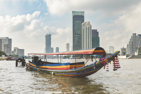 Thailand, Bangkok, typical boat on Chao Phraya river with city skyscrapers in background - WPEF01345