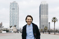 Spain, Barcelona, portrait of laughing man in the city with two skyscrapers in the background - JRFF02498