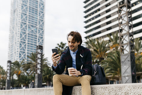 Spain, Barcelona, smiling man sitting in the city with takeaway coffee and cell phone - JRFF02501
