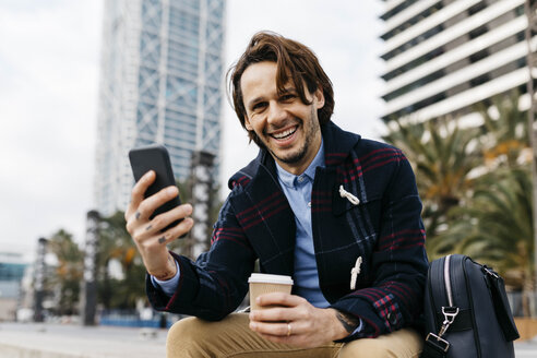 Spain, Barcelona, happy man sitting in the city with takeaway coffee and cell phone - JRFF02504