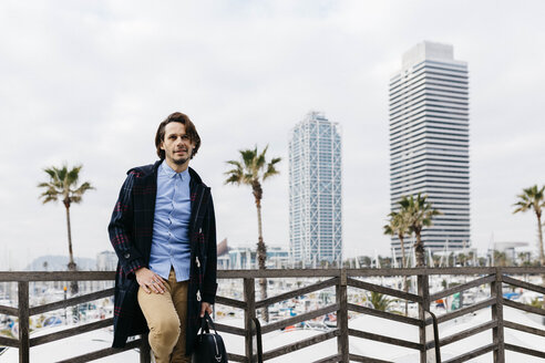 Spain, Barcelona, relaxed man after work with port and city background - JRFF02507