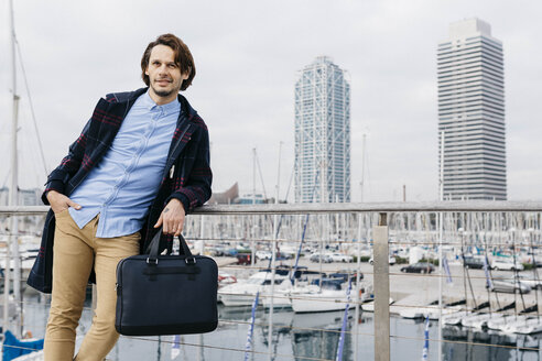 Spain, Barcelona. Handsome man relaxed after work with port and city background. - JRFF02513