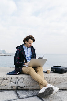 Spain, Barcelona, man sitting at the sea working with laptop and notebook - JRFF02519