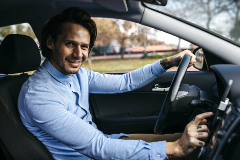 Portrait of smiling businessman driving car using cell phone as navigation system - JRFF02540