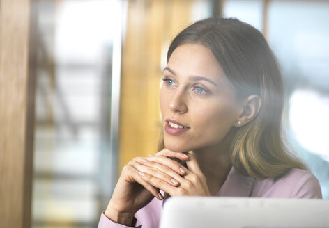 Confident businesswoman in office thinking - ABRF00264