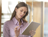 Businesswoman using tablet in office - ABRF00270
