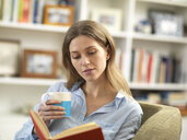 Young woman with a hot drink relaxing at home reading a book - ABRF00282