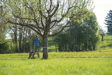 Girl balancing on a slackline in the countryside - SBOF01686