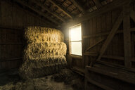 Traditional farm barn with bales of straws and light coming through window - SBOF01689
