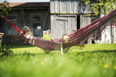 Two children relaxing in hammock in garden of a farm - SBOF01698