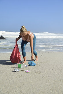 Pregnant woman cleaning the beach from plastic waste - ECPF00359