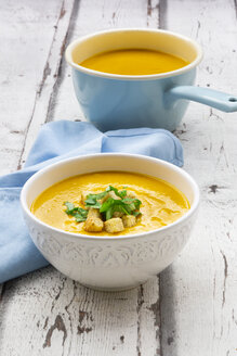 Bowl of sweet potato soup with mango, curcuma and coconut milk, croutons and basil - LVF07736