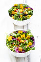 Mixed salad with roasted tofu, red cabbage, pomegranate seeds and curcuma in bowl on white wood - LVF07739