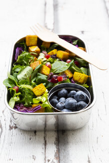 Mixed salad with roasted tofu, red cabbage, pomegranate seeds, blueberries and curcuma in lunch box - LVF07742
