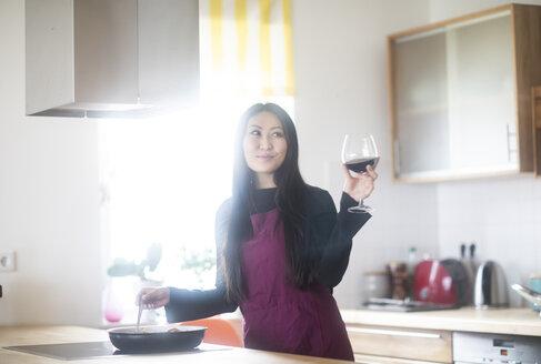 Junge Frau im schicken Kleid kochend in der Küche mit Rotwein - SGF02226