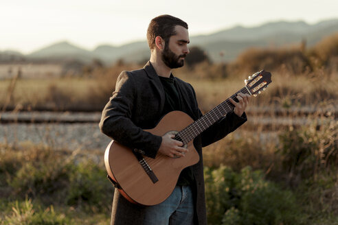 Male musician with beard playing the guitar in the countryside - LOTF00057