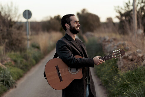 Male musician smiling and holding a guitar in a countryside road in the evening - LOTF00060