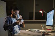 Designer drinking coffee and working late in office - HEROF14848