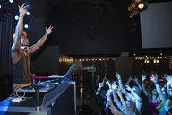Crowd cheering below DJ on nightclub stage - HEROF14899