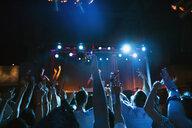 Crowd cheering for DJ on stage in nightclub - HEROF14935
