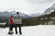 Couple snowshoeing and looking at snowy mountain view - HEROF14977