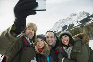 Couples taking selfie below snowy mountains - HEROF14995