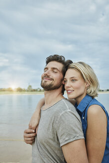Happy young couple hugging at the riverbank - RORF01676